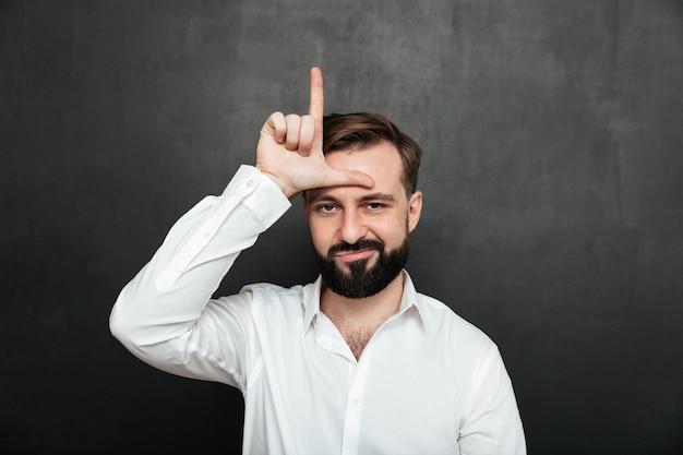 Portret nieszczęśliwego faceta 30s pozuje na kamerze i pokazuje nieudacznika znaka na jego czole nad grafitem