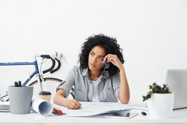 Portret nieszczęśliwego i zmęczonego młodego afro amerykańskiego architekta pracującego na plany