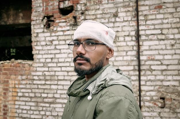 Portret nieszczęśliwego młodego mężczyzny z bliskiego wschodu z brodą z zabandażowaną głową, opuszczony budynek w ...