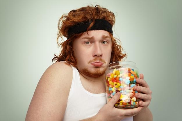 Portret nieszczęśliwego, otyłego, młodego rudowłosego europejczyka z nadwagą, noszącego opaskę do włosów i białą koszulkę bez rękawów po ćwiczeniach fizycznych, sfrustrowany, gdy nie może przestać jeść pysznych słodyczy