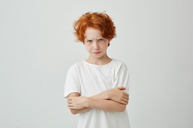 Portret nieszczęśliwego rudowłosego chłopca z piegami, patrząc ze zdenerwowanym wyrazem twarzy, skrzyżowane ręce niezadowolone z tego, że skarciła go mama.
