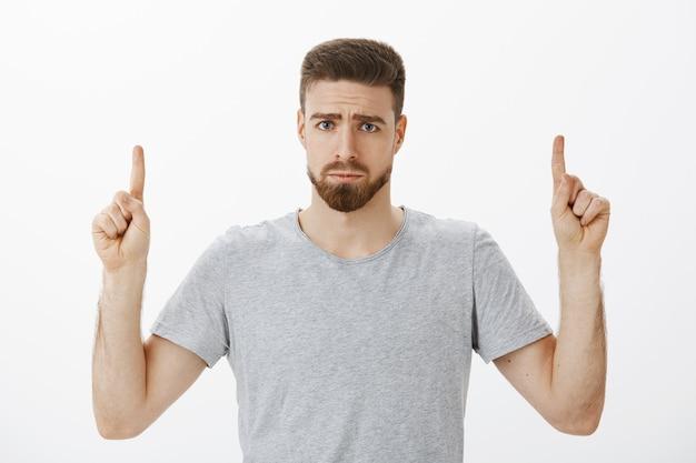 Portret nieszczęśliwego, smutnego i głupiego przystojnego mężczyzny z brodą i wąsami marszcząc brwi, robiąc ponury uśmiech skierowany w górę, wyrażając żal lub zazdrość stojąc niezadowolony na szarej ścianie