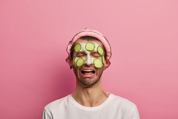 Portret nieszczęśliwego zdesperowanego mężczyzny męczy zabiegi kosmetyczne