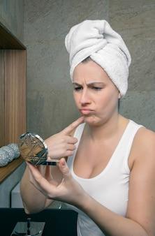 Portret nieszczęśliwej kobiety z ręcznikiem na włosach, patrząc w lustro, trądzik pryszcz na jej pięknej twarzy w łazience