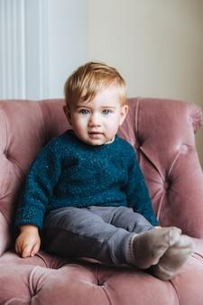 Portret niewinnego małego dziecka z niebieskimi oczami i pulchnymi policzkami, patrzy prosto w kamerę