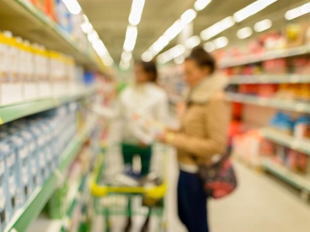 Portret niewyraźnych klientów robiących zakupy w supermarkecie z różnymi produktami na półkach