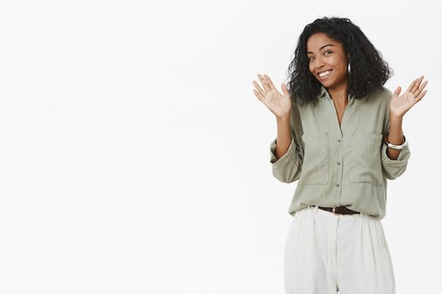 Portret niezaangażowanego, charyzmatycznego, młodego, ciemnoskórego pracodawcy w bluzce unoszącej dłonie