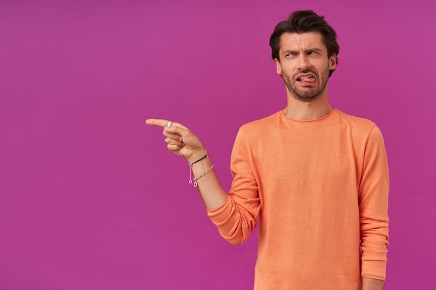 Portret niezadowolonego mężczyzny z brunetką i włosiem. na sobie pomarańczowy sweter. posiada bransoletki i pierścionki