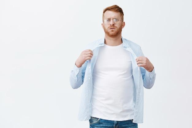 Portret niezadowolonego mężczyzny z rudymi włosami i brodą w okularach, cierpiącego z powodu letniej pogody, machającego koszulą do chłodnego ciała, wydychającego powietrze z upału