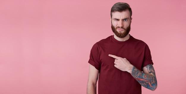 Portret niezadowolonego młodego przystojnego, rudego brodatego mężczyzny w czerwonej koszuli, chce zwrócić twoją uwagę na skopiowanie miejsca po lewej stronie, marszczy niezadowolony wyraz twarzy, stoi na różowym tle.