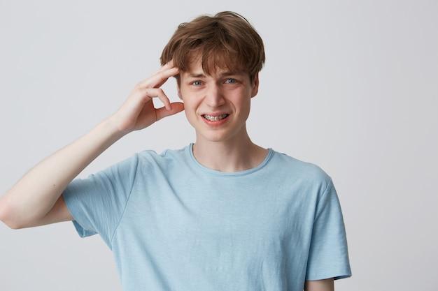 Portret niezadowolonego niezadowolonego młodzieńca z szelkami na zębach nosi niebieską koszulkę