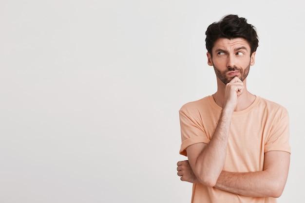 Portret niezadowolonego, niezadowolonego młodzieńca z włosiem nosi brzoskwiniową koszulkę, wygląda na zdenerwowanego i wskazuje na bok palcem odizolowanym na białym