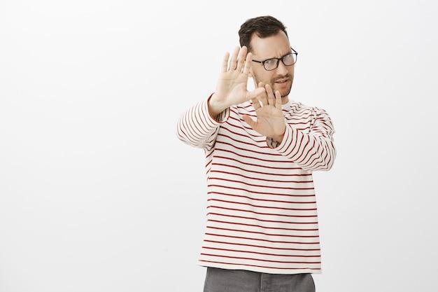 Portret niezadowolonego wybrednego mężczyzny z włosiem, wyciągającego dłonie w kierunku gestu nie lub zatrzymania, odrzucającego lub zasłaniającego twarz czymś obrzydliwym, stojącego zawiedzionego i obojętnego