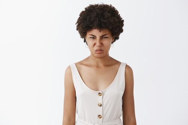 Portret niezadowolonej afroamerykanki wykręcającej twarz z niechęci i rozczarowania, marszczącej nos i marszczącej brwi z powodu okropnego zapachu lub spojrzenia, pozująca