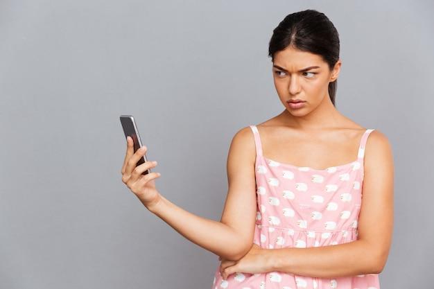 Portret niezadowolonej brunetki w różowej sukience robi zdjęcie selfie na smartfonie odizolowanym na szarej ścianie