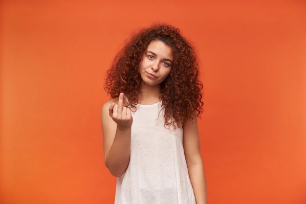 Portret niezadowolonej, dorosłej dziewczyny rude z kręconymi włosami. ubrana w białą bluzkę z odkrytymi ramionami. pokazuje znak pieprzenia. odpieprz się. pojedynczo na pomarańczowej ścianie