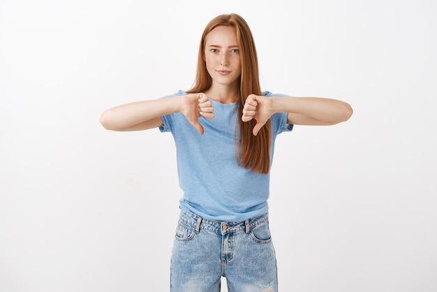 Portret niezadowolonej i niezadowolonej, przystojnej, apodyktycznej dziewczyny z rudymi włosami i piegami, marszczącej brwi i wykrzywiających usta w niezgodzie, pokazującej kciuki w dół, która nie lubi złego pomysłu