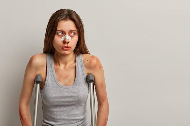 Portret niezadowolonej kobiety, która uległa wypadkowi, patrzy na bok