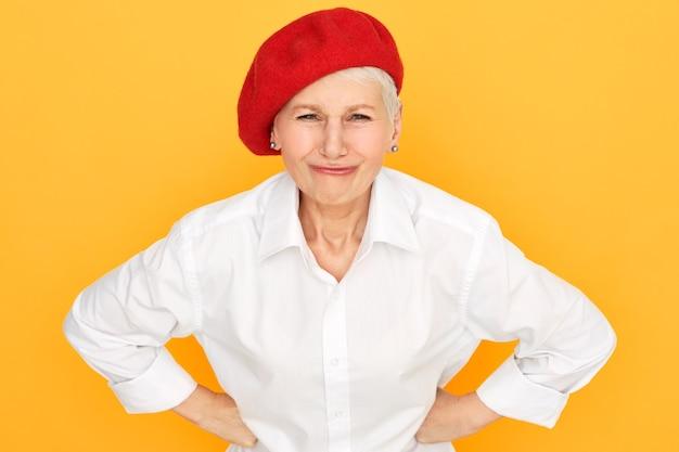 Portret niezadowolonej krótkowłosej emerytki w eleganckiej czerwonej czapeczce, trzymając się za ręce na jej talii