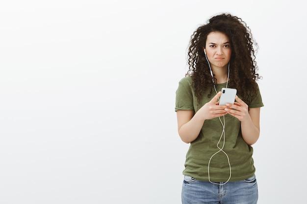 Portret niezadowolonej, niezadowolonej atrakcyjnej studentki z kręconymi brązowymi włosami, trzymającej smartfon i noszącej słuchawki, wyglądającej na niezadowoloną i smutną