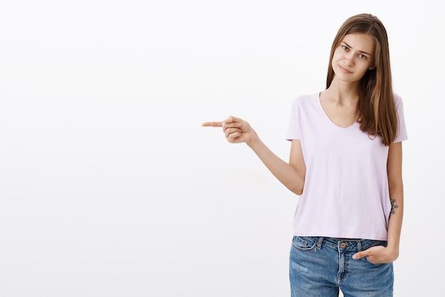 Portret niezadowolonej, niezadowolonej ślicznej snobistycznej dziewczyny z brązowymi włosami w koszulce, marszczącej brwi i uśmiechającej się z niechęci, wskazując w lewo niezadowoloną i niezainteresowaną