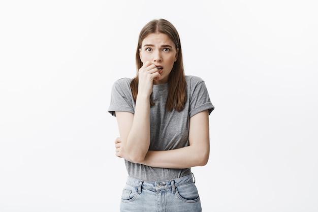 Portret niezadowolonej pięknej młodej studentki europejskiej o ciemnych włosach i brązowych oczach w modnych ubraniach gryzie palce, z przestraszonym wyrazem twarzy, martwiąc się, że zaszła w ciążę.
