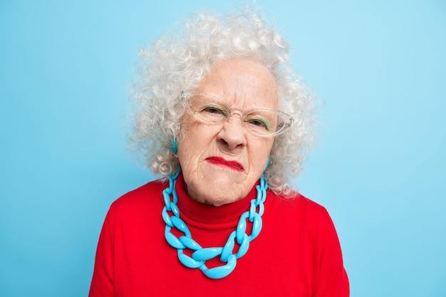 Portret niezadowolonej starszej kobiety wygląda z nieszczęśliwym zirytowanym wyrazem twarzy