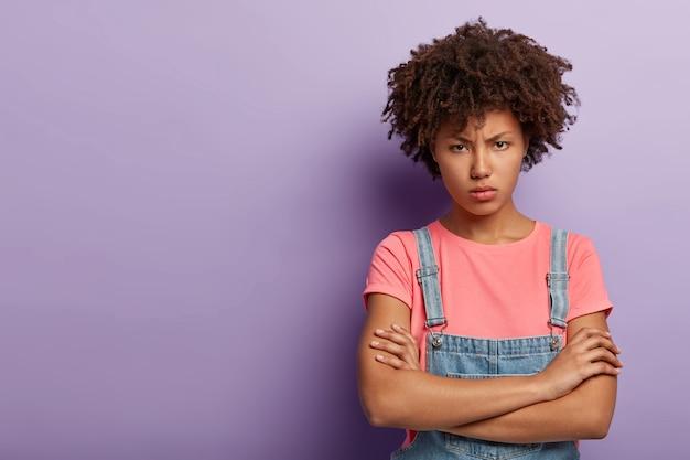 Portret niezadowolonej złej młodej kobiety z afro pozowanie w kombinezonie
