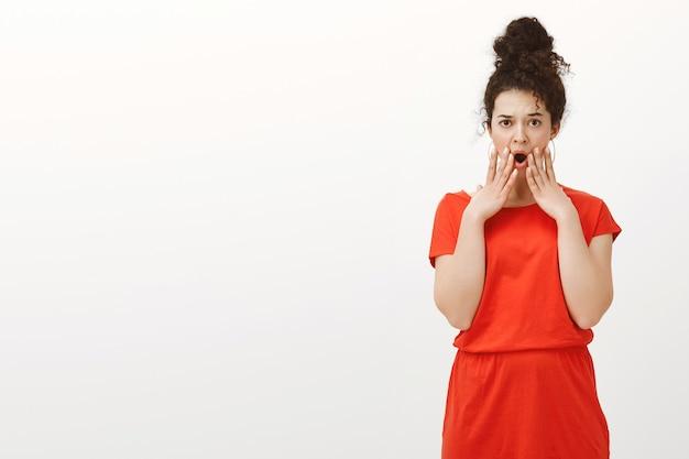 Portret niezadowolonej, zszokowanej kobiety z kręconymi włosami w stylowej sukience na co dzień, trzymającej rękę w pobliżu otwartych ust