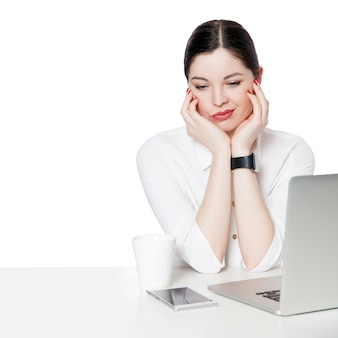 Portret niezadowolony lub smutny brunetka bizneswoman w białej koszuli siedzi z laptopem dotykając jej twarzy i myślenia lub zdezorientowany i myślący. kryty strzał studio, odizolowane w białym tle.