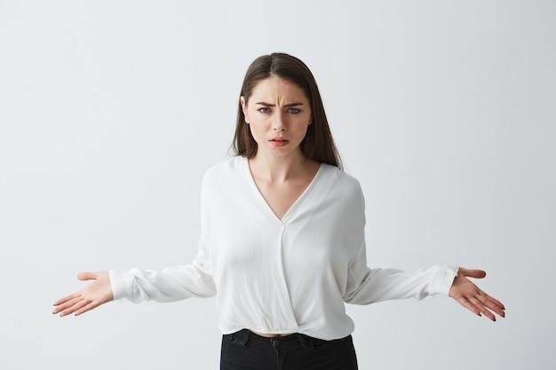 Portret niezadowolony młody bizneswoman rozprzestrzenia ręki.