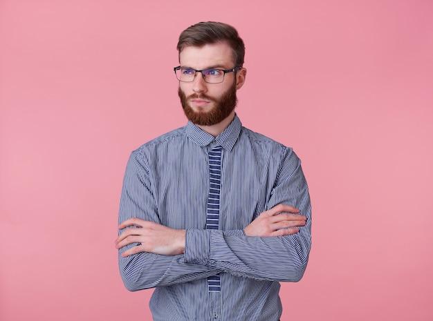 Portret niezadowolony, myślący, młody, przystojny, brodaty mężczyzna w okularach i koszuli w paski, stoi na różowym tle, ze skrzyżowanymi rękami, odwróć wzrok.