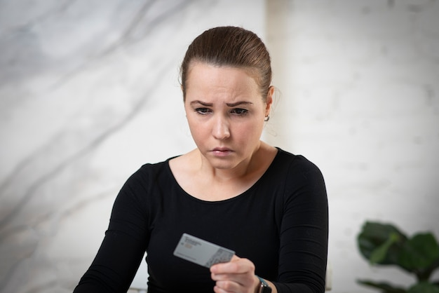 Portret niezadowolony zmartwiony zły smutny zdenerwowany dziewczyna, młoda sfrustrowana rozczarowana kobieta trzyma kredyt