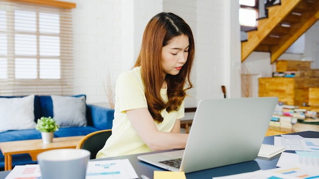 Portret niezależnych azjatyckich kobiet nosić przy użyciu laptopa pracującego w salonie w domu. praca z domu, praca zdalna, samoizolacja, dystans społeczny, kwarantanna w celu zapobiegania koronawirusom.