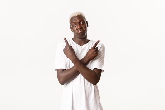 Portret niezdecydowanego faceta afroamerykanów, wzruszając ramionami i wskazując palcami w bok