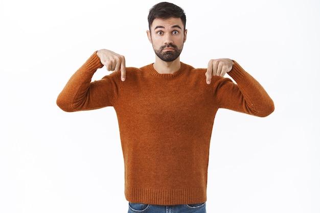Portret niezdecydowanego przystojnego brodatego mężczyzny zadającego pytanie o produkt, wskazującego palcami w dół niepewnego, konsultującego się z dziewczyną, pytającego o opinię, biała ściana