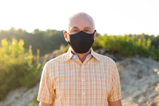 Portret noszenia maski medycznej starszy mężczyzna. koncepcja koronawirusa. ochrona dróg oddechowych