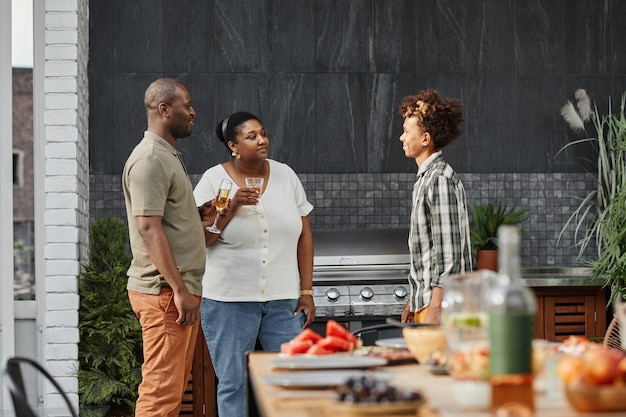 Portret nowoczesnej afrykańskiej rodziny z nastoletnim synem jedzącym kolację na tarasie na świeżym powietrzu kopiuje s...