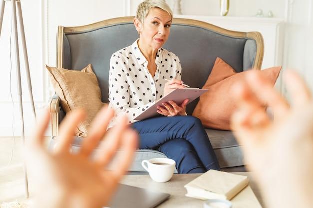 Portret nowoczesnej blond kaukaskiej psycholog, która prowadzi sesję terapeutyczną ze swoim klientem