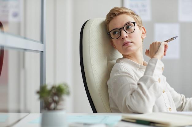 Portret nowoczesnej krótkowłosej kobiety w okularach odwracając zamyślony wzrok siedząc w dużym krześle biurowym w pracy, koncepcja kobiecego szefa, kopia przestrzeń