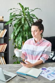 Portret nowoczesnej młodej kobiety, ciesząc się kawą i przy użyciu smartfona podczas pracy w domu, miejsce