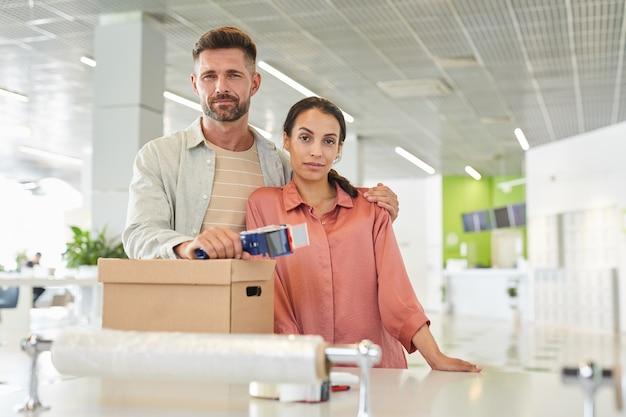 Portret nowoczesnej pary dla dorosłych podczas pakowania kartonów w magazynie, miejsce na kopię