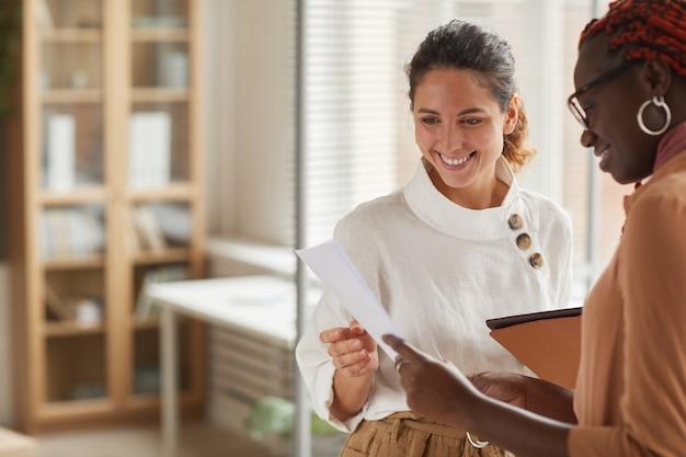 Portret nowoczesnej udanej bizneswoman rozmawia ze stażystką w pasie i uśmiecha się radośnie, stojąc we wnętrzu biura, kopia przestrzeń