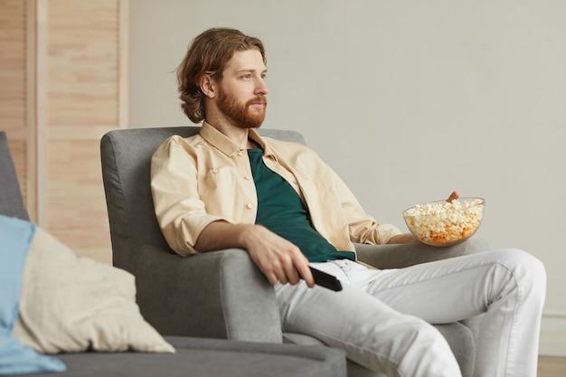 Portret nowoczesny brodaty mężczyzna ogląda telewizję w domu, relaksując się w wygodnym fotelu i trzymając miskę popcornu