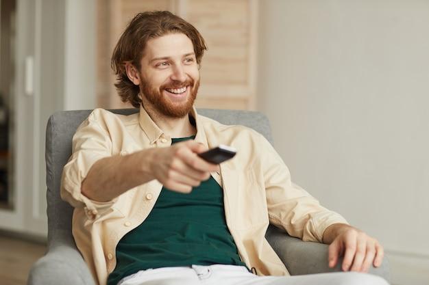 Portret nowoczesny brodaty mężczyzna ogląda telewizję w domu, relaksując się w wygodnym fotelu i trzymając pilota