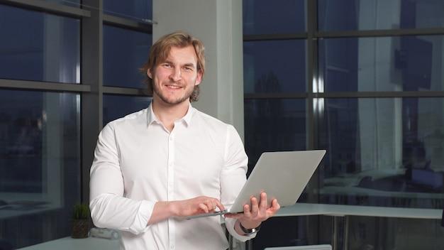 Portret nowożytny męski freelancer z laptopem w rękach