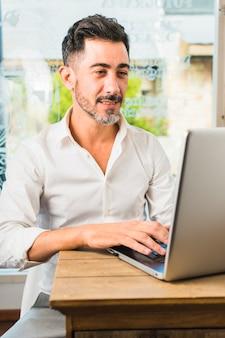 Portret nowożytny mężczyzna obsiadanie w cukiernianym używa laptopie