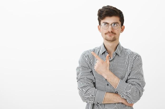 Portret obojętnego, niezaskoczonego nerdy faceta z wąsami, wskazującego i patrzącego w lewy górny róg z napiętym uśmiechem, niezadowolonego bez przejmowania się tematem, stojącego nad szarą ścianą