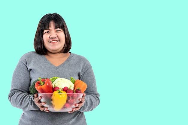Portret obrazów azjatyckich atrakcyjnej kobiety tłuszczu trzymającej szklaną miskę zawiera owoce i świeże warzywa na zielonym miękkim tle na białym tle, do kobiety ze zdrową żywnością i koncepcją odchudzania.