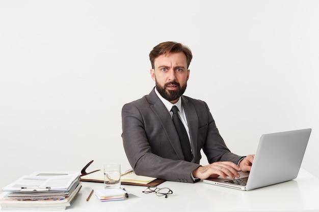 Portret oburzonego kierownika biura, który odwrócił się od pracy, siedzący przy biurku w biurze, pracujący dla swojego laptopa, ubrany w drogi garnitur z krawatem.